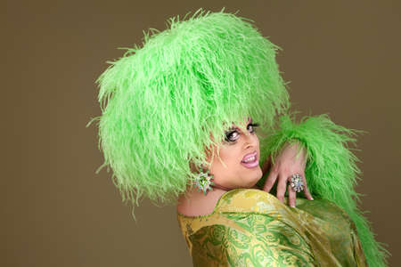 Drag queen with makeup and green fluffy wig smiles  photo