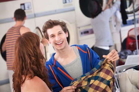 Handsome young Caucasian man with girlfriend smiles in the laundromat Stock Photo - 9960864