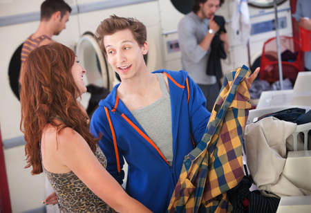 Young handsome Caucasian man flirts with beautiful lady in laundromat photo