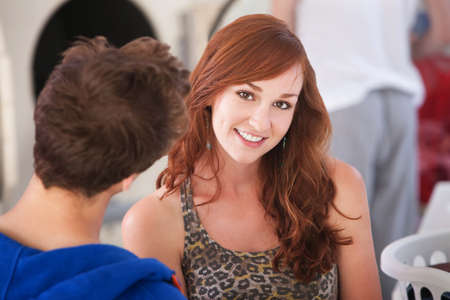 laundromat: Beautiful young Caucasian lady with boyfriend smiles in laundromat