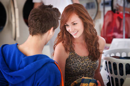 Gorgeous young Caucasian lady flirts with a man in laundromat  photo