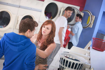 laundromat: Beautiful young Caucasian lady argues with boyfriend in laundromat Stock Photo