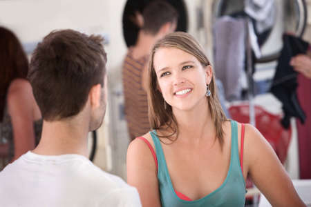 Beautiful young woman with boyfriend smiles in laundromat photo