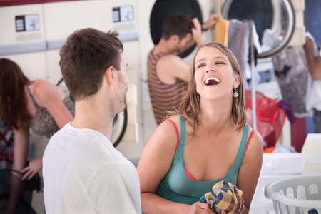 Happy young woman with boyfriend laughs out loud in the laundromat Фото со стока - 9960878