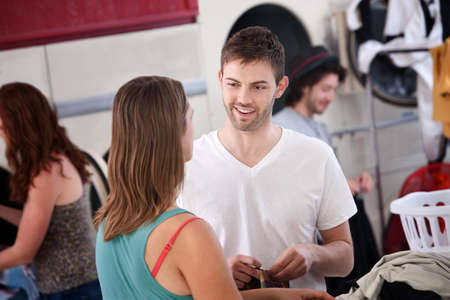 Handsome young Caucasian man talks with woman in laundromat photo