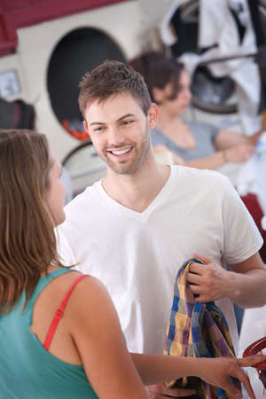 Young handsome Caucasian man flirts with woman in laundromat photo