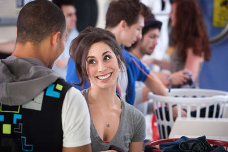 Young Caucasian lady with boyfriend grins in laundromat photo
