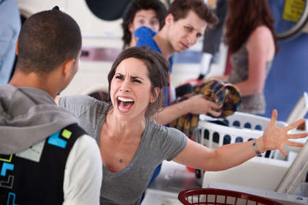 annoy: Frustrated young woman yells at a man in the laundromat