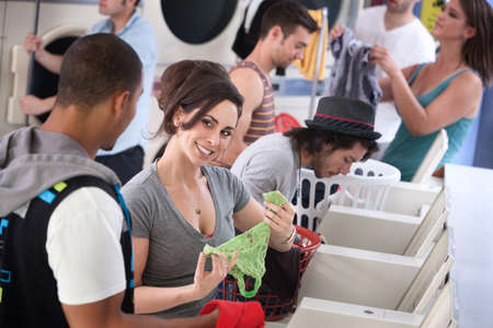 laundromat: Woman holds panties and flirts with man in laundromat Stock Photo