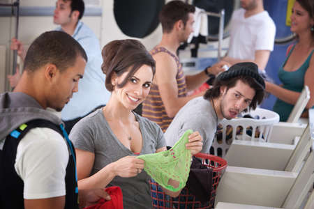 Beautiful Caucasian stares at handsome Black man with panties in her hands at the Laundromat photo