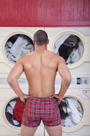 Muscular man in boxer shorts waits in front of washing machines