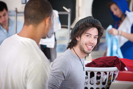 laundromat: Young handsome man with his friend smiles in the laundromat