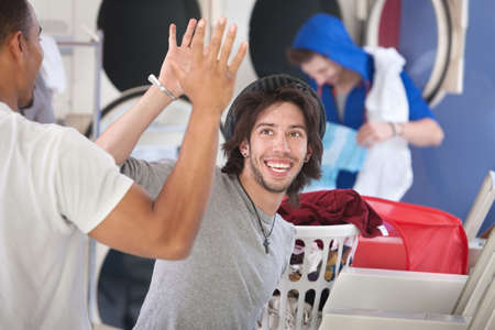 laundromat: Two happy young friends high five in the laundromat