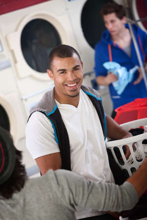 laundromat: Young muscular Latino man smiles in laundromat