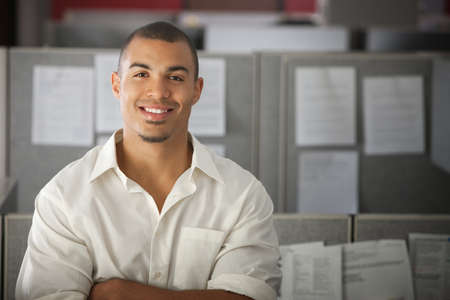 Confident office worker smiles in his office cubicle  Imagens