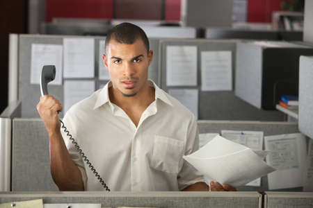 Frustrated office worker with papers holds a phone away from his ear photo