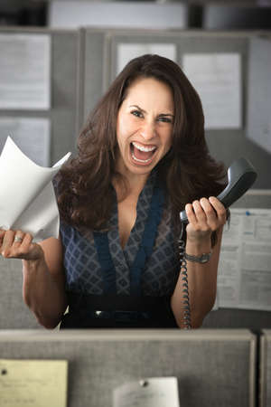 Screaming woman with phone and notes in office cubicle photo
