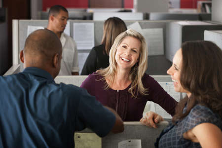 Office workers laugh at a joke shared by colleague Stock Photo