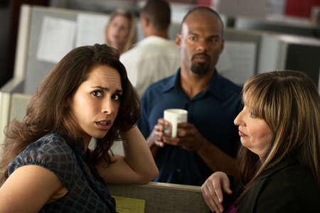 Worried woman office worker chats with friends at her cubicle photo
