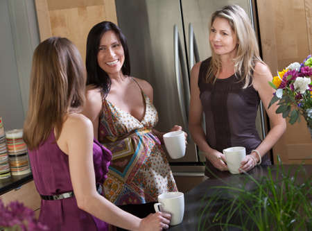 Pregnant woman with mug in kitchen with friends photo