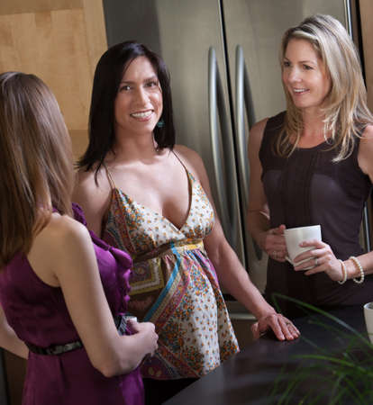 Happy pregnant lady smiles with her friends in kitchen  photo