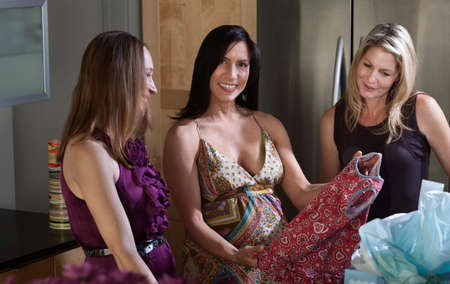 Happy pregnant lady recieves baby clothes as gift from friends  photo