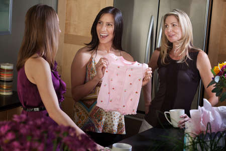 Excited pregnant lady recieves baby clothes as present from friend photo