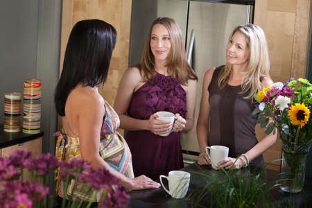 Two pregnant women in a kitchen talk with their friend photo