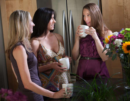 Two pregnant women enjoy coffee or tea with friend in a kitchen  photo