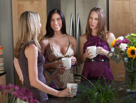 Two happy pregnant women at different points in their pregnancy enjoy a cup of coffee with friend photo