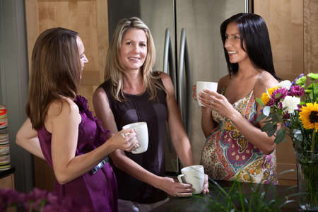 Two pregnant women enjoy cup of coffee or tea with their blonde friend photo