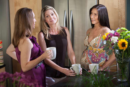 Two pregnant women hold mugs mugs with a friend in the kitchen photo