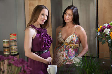 Two beautiful pregnant women at different points in their pregnancy in a kitchen