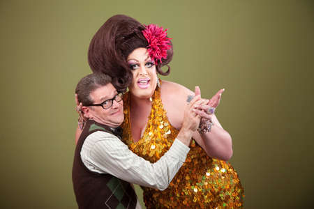 Drag queen and Caucasian nerd on green background hold hands