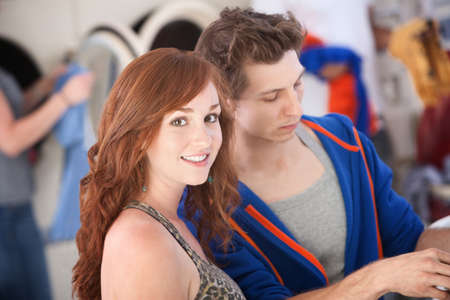 Beautiful woman with boyfriend smiles in the laundromat photo