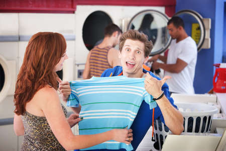 Unhappy man with girlfriend holds a shrunken t-shirt in laundromat Banque d'images