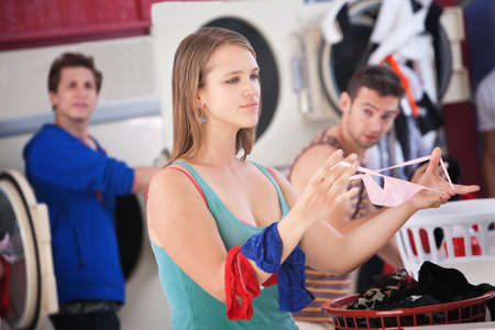 Beautiful young Caucasian lady folds underwear in the laundromat