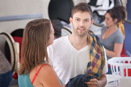 Handsome young Caucasian man with his girlfriend in laundromat photo
