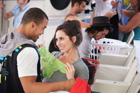 Young lady holding underwear in front of man in laundromat photo