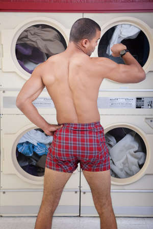 Partially dressed man in Laundromat checks the time photo