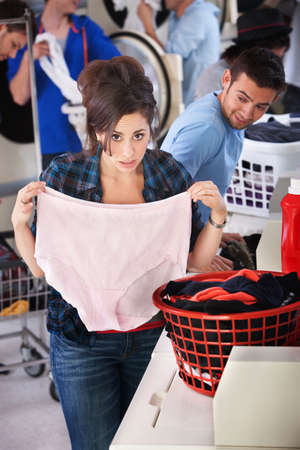 pink panties: Worried young lady holds oversize granny panties in laundromat