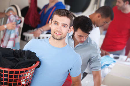 Handsome young blue-eyed Caucasian man in a laundromat photo