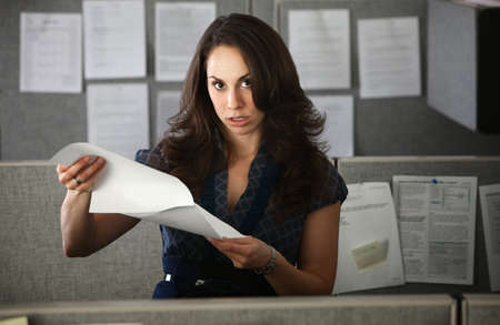 Frustrated woman office worker holding documents stands in cubicle photo