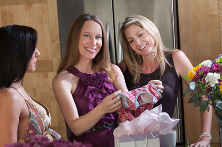 Expecting mom with friends holds baby clothes  photo