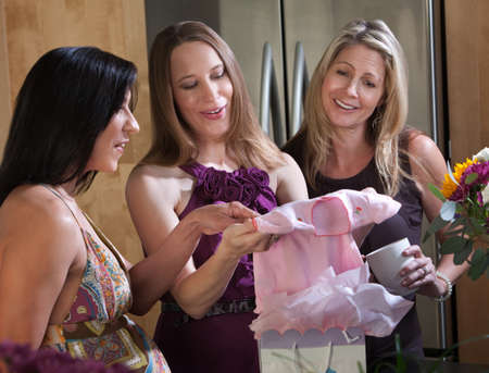 Expectant mom recieves baby clothes gift for baby shower photo