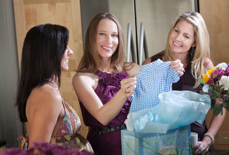 Happy pregnant woman and friends with boy baby clothes gift photo