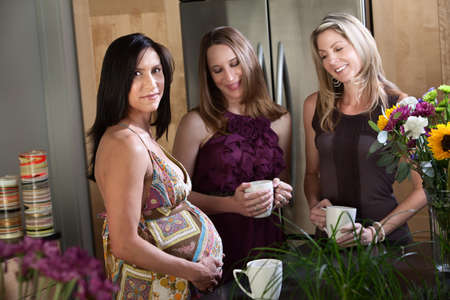 Pregnant woman with friends with tea in kitchen photo
