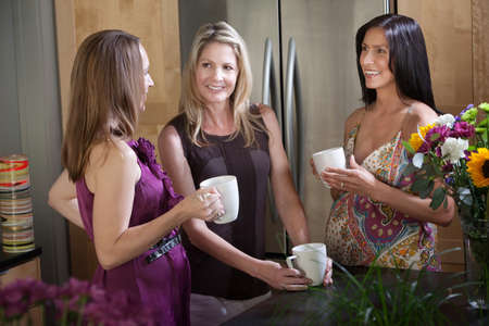 Two happy pregnant women with friend in a kitchen photo