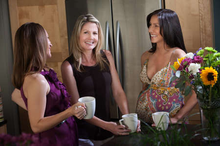 Two happy pregnant women at different points in their pregnancy enjoys a cup of coffee or tea with friend in kitchen photo