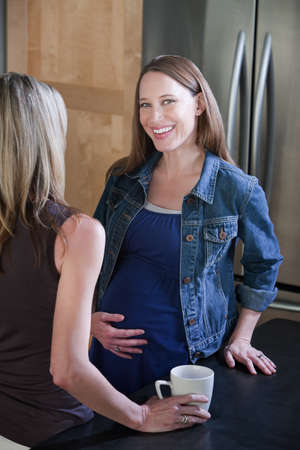 Smiling pregnant woman holds her tummy in kitchen photo
